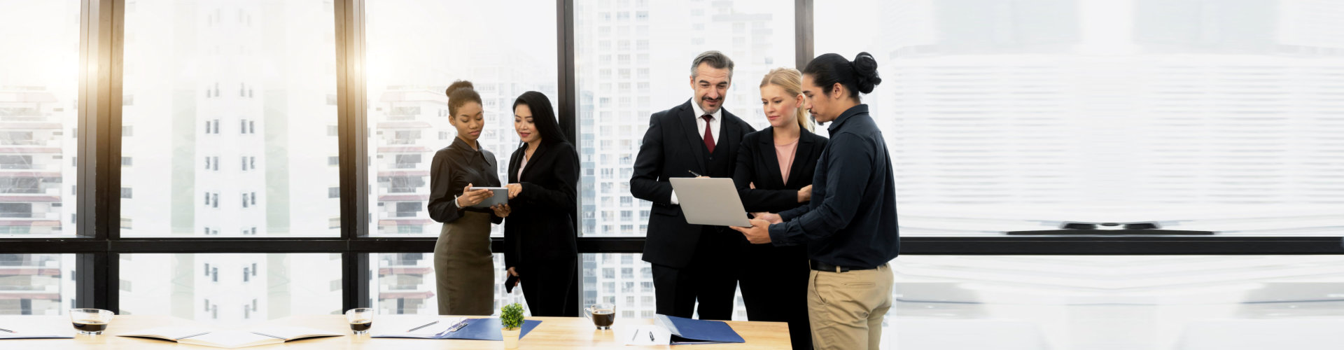 employees looking at data on a tablet and laptop computer