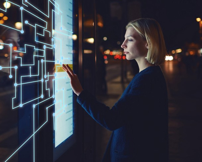 a woman looking at a digital signage