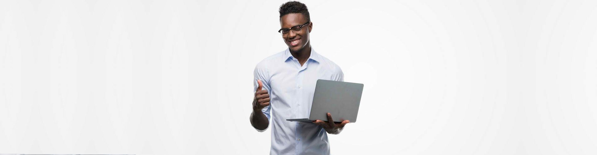 a man holding a laptop smiling